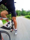 路自行车;骑一辆赛跑的自行车的男性骑自行车者下坡 免版税库存图片