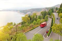 路蛇纹石 山弯曲道路在陶尔米纳  红色公共汽车 西西里岛,意大利的海岛 库存图片