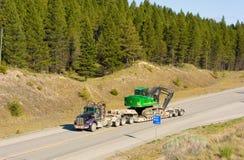 路被交付的挖掘机在北加拿大 免版税库存照片