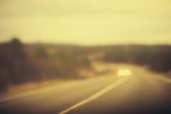 路被弄脏的轨道和汽车车灯背景 免版税库存照片
