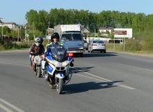 路警察的摩托化军队的官员扣留了在滑行车的十几岁 免版税库存照片