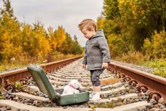 路轨的一个男孩在森林中包装在一古色古香的减速火箭的valise的一个玩具兔宝宝 免版税库存图片