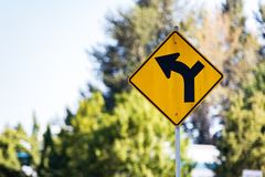 路转动定向路牌与树 图库摄影