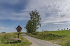 路边十字架和长木凳在Grà ¼的b巴法力亚森林里Grafenau 免版税库存照片