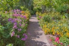 路通过夏天四季不断的庭院标示用花 库存图片