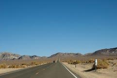 直路部分通过沙漠和明白蓝天 免版税图库摄影