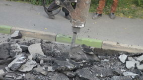 路面的修理部分 在挖掘机毁坏的沥青层数的水力锤子破碎机在遏制石头附近 影视素材