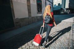 路面的少妇带着一个红色手提箱 查出的背面图白色 库存照片