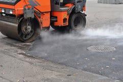 路维修服务,压紧机放置沥青 修理路面和放置新的沥青 库存图片