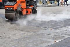 路维修服务,压紧机放置沥青 在放置的长跑训练sphalt 修理路面和放置新的沥青修补的方法 免版税库存图片