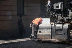路建设中,操作员在摊铺机运转 免版税库存照片