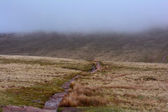 路/道路在有雾的天气,笔y爱好者峰顶,布雷肯比肯斯山,威尔士,英国 库存图片