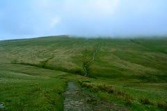 路/道路在用低云盖的青山,笔y爱好者峰顶,布雷肯比肯斯山,威尔士,英国 免版税库存照片