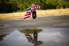 跳一个年轻的男孩,当拿着显示他自己的国家的时美国国旗爱国心,团结状态 免版税库存照片