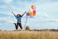 跳与五颜六色的气球的妇女在草甸 库存照片