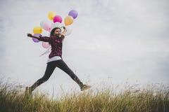 跳与五颜六色的玩具的愉快的行家女孩迅速增加户外 免版税库存图片