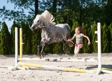 跳与小马的女孩 免版税库存照片