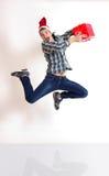 跳与礼品的圣诞老人盖帽的年轻人 免版税库存照片
