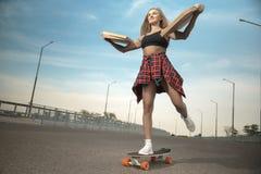 跳与headphonesGirl不滑板或longboard的一个滑板的女孩在城市运送比萨 免版税图库摄影