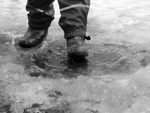 跳为在路的水坑的孩子在最后冬天的解冻 免版税图库摄影