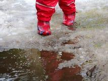 跳为在路的水坑的孩子在最后冬天的解冻 免版税库存图片