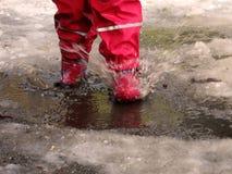 跳为在路的水坑的孩子在最后冬天的解冻 免版税库存照片