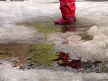 跳为在路的水坑的孩子在最后冬天的解冻 库存图片