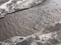 跳为在路的水坑的孩子在最后冬天的解冻 库存照片