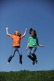 跳二个年轻人的女孩 免版税库存图片
