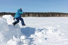 跳从雪的一座未完成的园屋顶的小屋的男孩 免版税库存照片