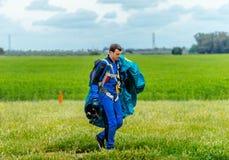 跳伞运动员在登陆以后运载一个降伞 免版税库存照片