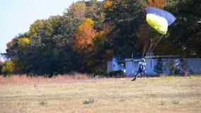 跳伞运动员飞行与降伞和登陆在地面上 慢的行动 股票录像