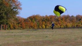 跳伞运动员飞行与降伞和登陆在地面上 股票录像