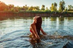 跳出水和做飞溅的比基尼泳装的年轻女人 ?? 库存图片
