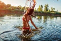 跳出水和做飞溅的比基尼泳装的年轻女人 ?? 库存照片