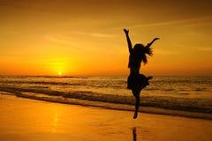 跳到日落的愉快的妇女在泰国 免版税库存照片