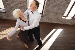 跳华尔兹在舞厅的快乐的年迈的夫妇 免版税库存图片