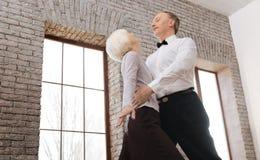 跳华尔兹在舞厅的逗人喜爱的高兴老化夫妇 免版税库存图片