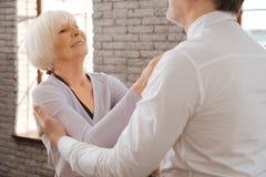 跳华尔兹在舞蹈演播室的微笑的年迈的夫妇 免版税图库摄影