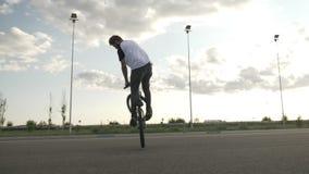 跳和执行在他的自行车的老练的青少年的骑自行车的人空中回旋行使自由式欺骗室外- 股票视频