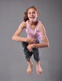 跳和跳舞在演播室的健康年轻愉快的微笑的十几岁的女孩 行使与跳跃的孩子在灰色背景 免版税图库摄影