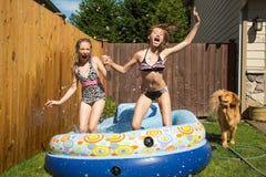 跳在一个可膨胀的水池的孩子 库存照片