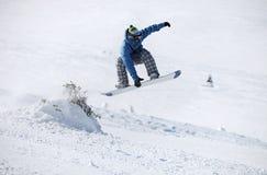 跳在一个多雪的倾斜的挡雪板 库存图片
