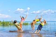 跳在一个大湖的孩子 库存照片