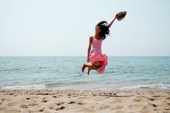 跳在一个热带海滩的妇女 免版税库存图片