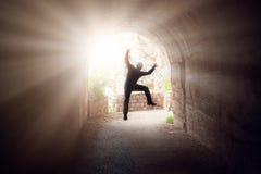 跳在一个黑暗的隧道的人 免版税库存图片