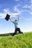跳在一个绿色草甸的男孩 免版税库存图片