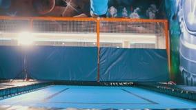 跳在一张绷床的年轻可爱的运动女孩在体育中心,推开并且登陆用不同的部分  股票视频