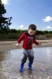 跳在与他新的起动的一个水坑的小孩 免版税库存图片
