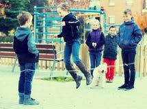 跳在中国人跳跃的有弹性绳索的孩子在围场 免版税库存照片